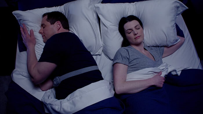 Couple sleeping in bed, one is wearing the Snoring Relief Band